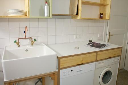 Ansicht Spülbecken aus Porzellan, Wasserhahn Kupferrohr Eigenbau, Spülkorpus, Waschmaschinen- und Spülmaschinenschrank mit zwei Schubkästen.